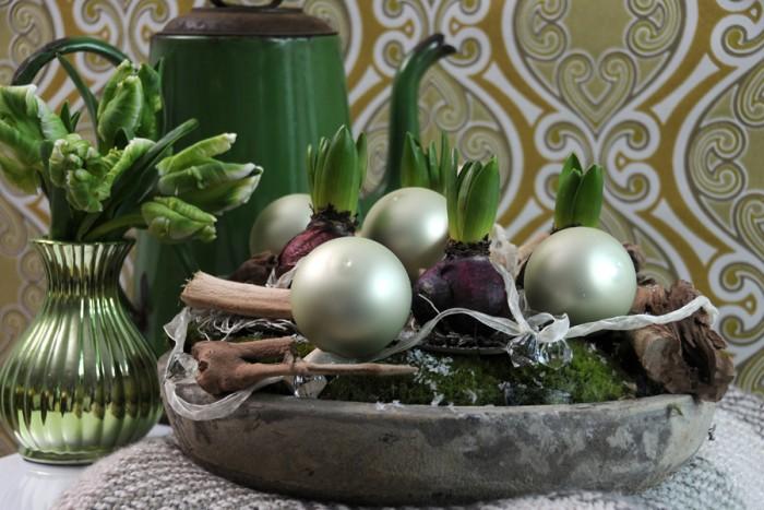 Arrangemang med lökar av hyacint, mossa och och julgranskulor i en skål.