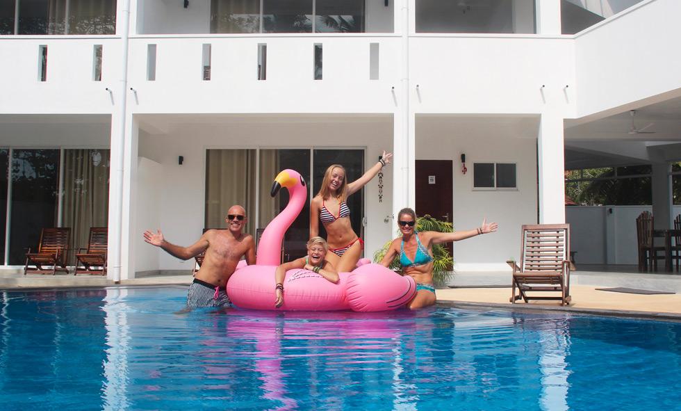Familjen Ternön badar i pool med uppblåsbar rosa flamingo.