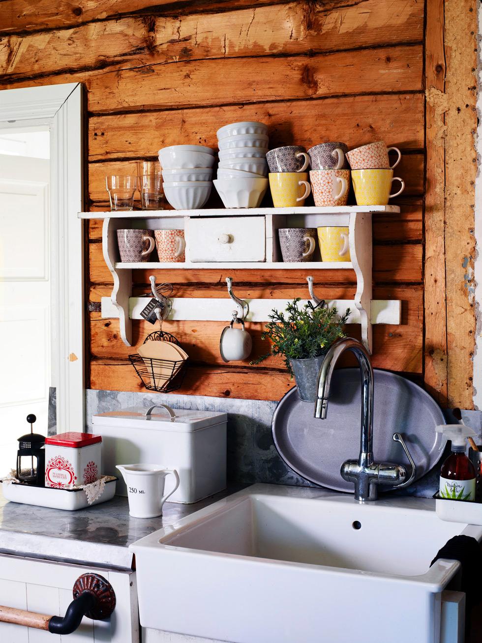 Vit porslinsdiskho i lantkök med timrad vägg.