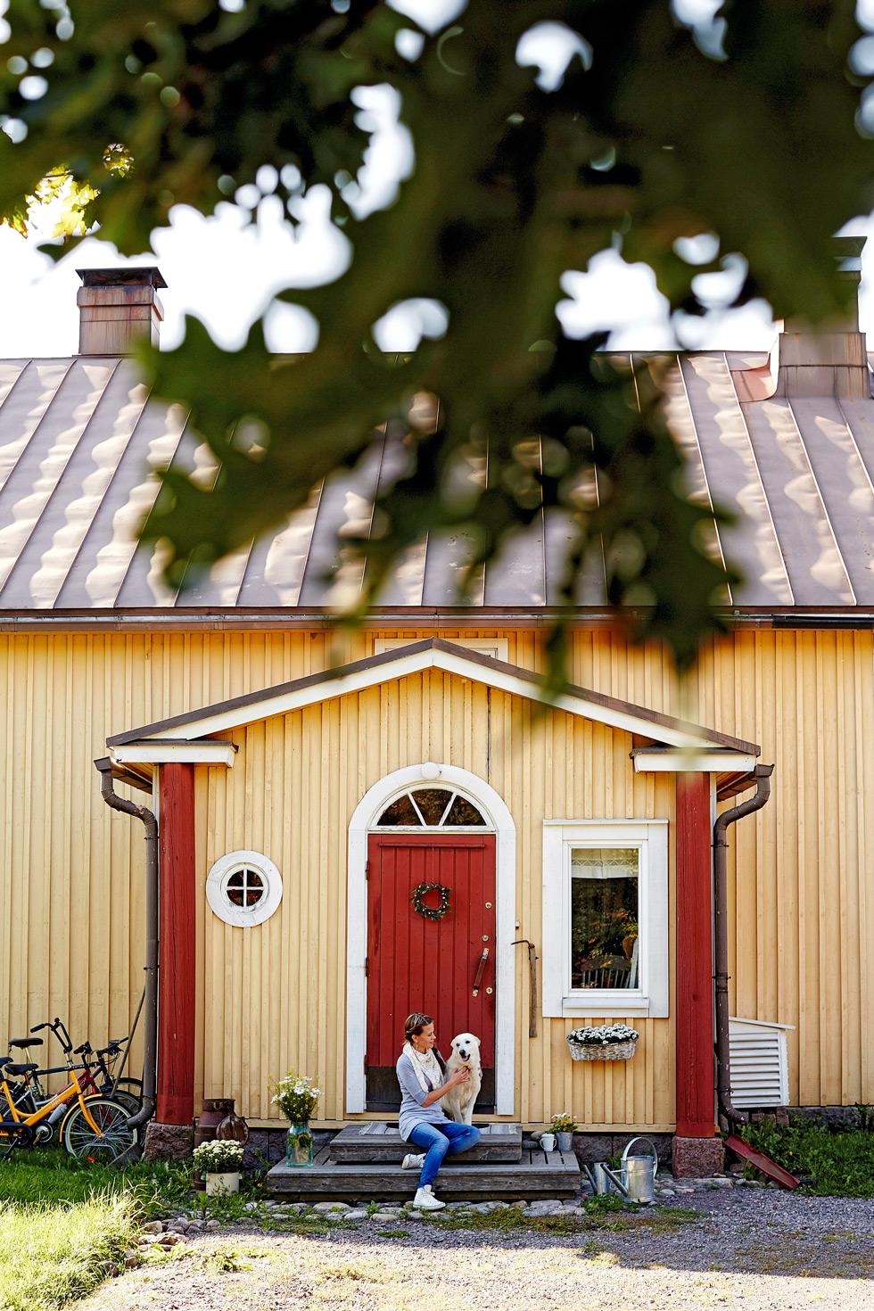 Gul gård med röd dörr.