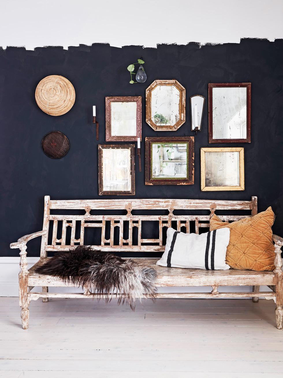 Träsoffa framför målad svart vägg med många speglar.