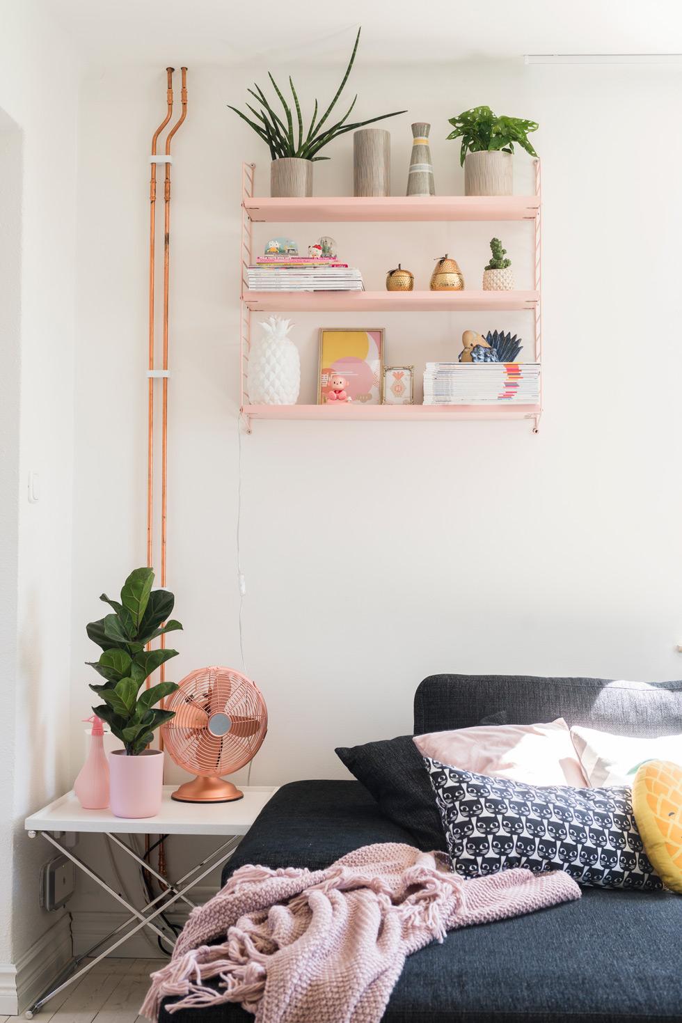 Ovanför soffan finns en rosa stringhylla.
