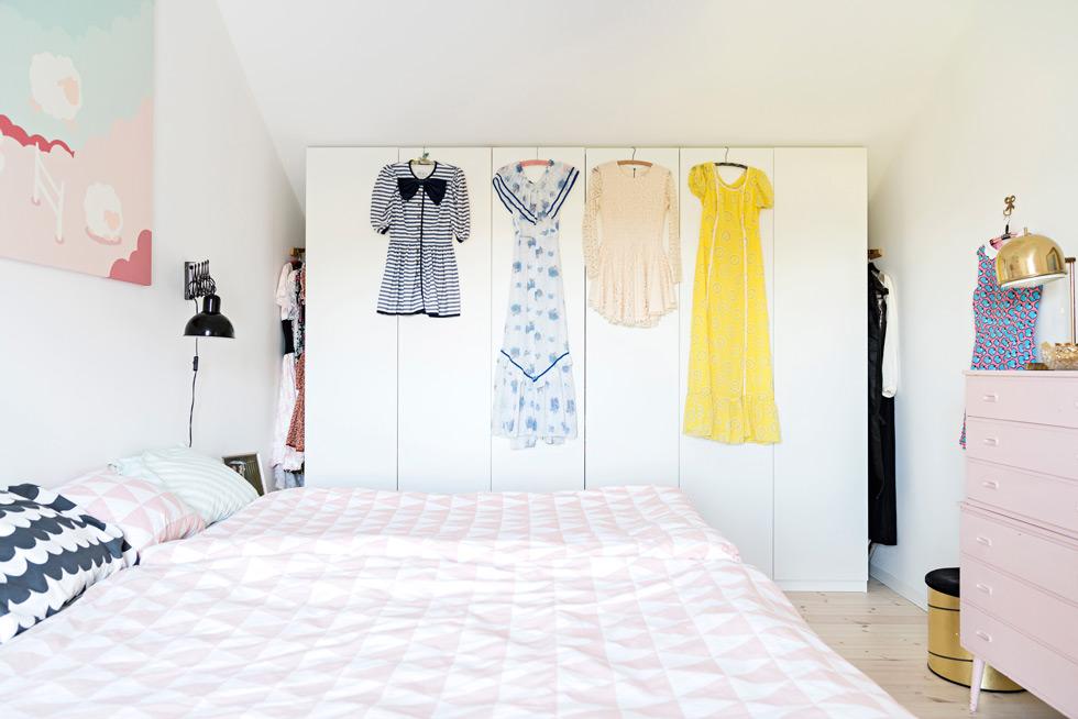 Sovrum med klänningar som hänger på galgar på garderobens utsida.