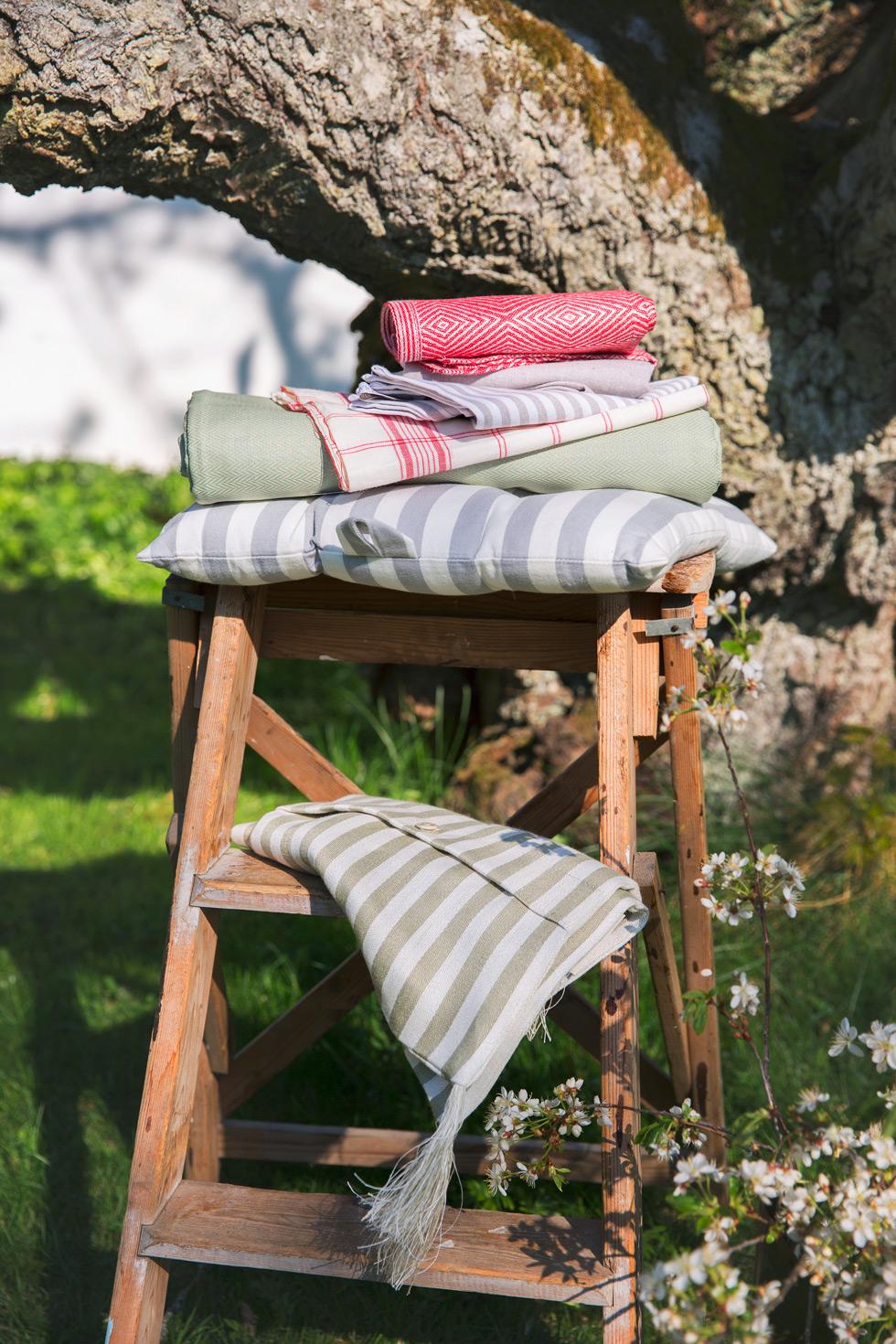 Textilier och dyna på liten stege i trädgården